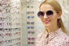 La jeune femme choisit des verres solaires dans le magasin d'opticien photographie stock libre de droits