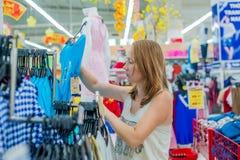La jeune femme choisit la chemise dans la boutique photo stock