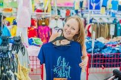 La jeune femme choisit la chemise dans la boutique photo libre de droits