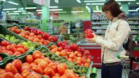 La jeune femme choisit le poivron rouge mûr achetant les légumes frais dans un supermarché banque de vidéos