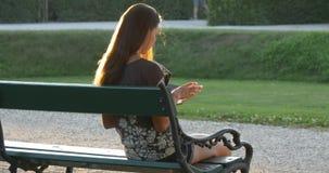 La jeune femme choisit un livre dans le lecteur électronique en parc clips vidéos