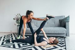 La jeune femme convenable faisant l'étirage s'exerce avec l'aide de l'entraîneur personnel à la maison Photographie stock libre de droits