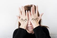 La jeune femme couvre ses yeux de ses paumes Yeux peints sur sa main photos libres de droits