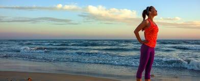 La jeune femme décontractée dans les sports embrayent sur le littoral au coucher du soleil photos libres de droits