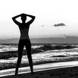 La jeune femme décontractée se tenant dans les sports embrayent sur le littoral image libre de droits
