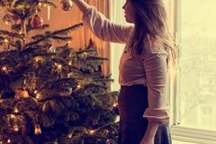 La jeune femme décore un arbre de Noël, vacances de tradition photo stock