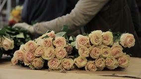 La jeune femme découpe des feuilles et des tiges des roses dans le salon de fleur banque de vidéos