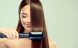 La jeune femme démontre le processus du redressage de cheveux Photographie stock libre de droits