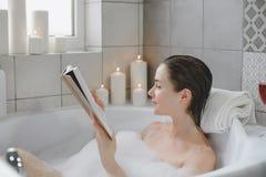 La jeune femme détend dans un bain chaud complètement de mousse image stock