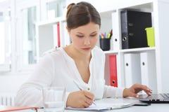 La jeune femme d'affaires asiatique avec l'ordinateur portable écrit sur un document à son bureau images libres de droits
