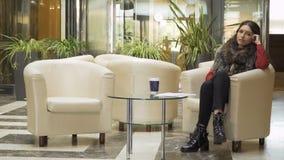 La jeune femme d'affaires attend dans le lobby de l'hôtel quand le directeur viennent chez elle banque de vidéos