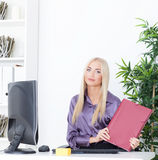 La jeune femme d'affaires blonde avec le dossier s'assied à la table au bureau Images libres de droits