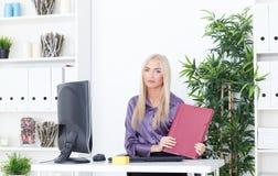 La jeune femme d'affaires blonde avec le dossier s'assied à la table au bureau Image libre de droits