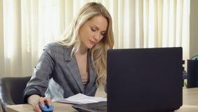 La jeune femme d'affaires dans le costume travaille avec des documents à l'ordinateur dans le bureau photo stock