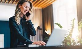 La jeune femme d'affaires de sourire dans le chemisier noir se tient d'intérieur, travaillant sur l'ordinateur, tout en parlant a photo stock