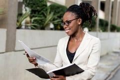 La jeune femme d'affaires de sourire des fichiers de recopie dehors Photographie stock libre de droits