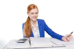 La jeune femme d'affaires est calculante et écrivante sur un papier Image libre de droits