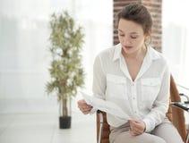 La jeune femme d'affaires lit une feuille de travail Image libre de droits