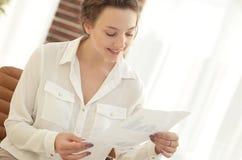 La jeune femme d'affaires lit une feuille de travail Photographie stock libre de droits