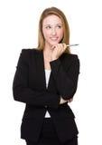 La jeune femme d'affaires pensent à une idée avec tenir un stylo image stock