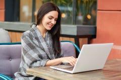 La jeune femme d'affaires réussie travaille sur l'ordinateur portable, vérifie la base de données sur la boîte d'email, emploie l photos stock