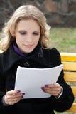 La jeune femme d'affaires regarde dans le papier Images stock
