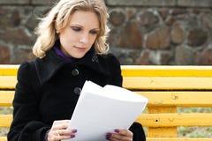 La jeune femme d'affaires regarde dans le papier Images libres de droits