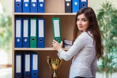 La jeune femme d'affaires se tenant à côté de l'étagère photo libre de droits