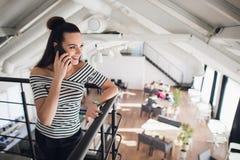 La jeune femme d'affaires se tient en café et parle au téléphone portable La fille attend les amis, collègues dans le restaurant Image libre de droits