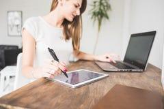 La jeune femme d'affaires travaillant à la maison et dessine sur le comprimé Espace de travail scandinave créatif de style photo libre de droits