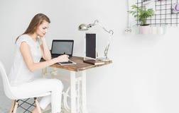 La jeune femme d'affaires travaillant à la maison et dessine sur le comprimé Espace de travail scandinave créatif de style images stock