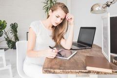 La jeune femme d'affaires travaillant à la maison et dessine sur le comprimé Espace de travail scandinave créatif de style photos libres de droits