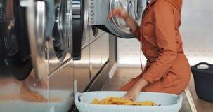 La jeune femme d'Afro-am?ricain s'assied devant une machine ? laver et emporte des v?tements de blanchisserie Libre service publi banque de vidéos