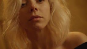 La jeune femme d'une chevelure blonde attirante avec les yeux bleus grands ouverts regarde dans l'appareil-photo banque de vidéos