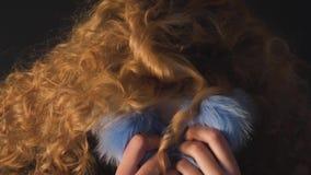 La jeune femme d'une chevelure bouclée cache son oui dans un collier de fourrure banque de vidéos