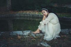 La jeune femme dans la décoration romantique de robe et de cheveux s'asseyent par l'étang images libres de droits