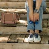 La jeune femme dans des blues-jean, les espadrilles rayées s'assied sur vieux s en bois Photographie stock