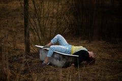 La jeune femme dans des vêtements prend un vieux bain vide au milieu d'une forêt photos stock