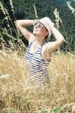 La jeune femme dans l'équipement de marin sourit au soleil avec des mains derrière Image stock