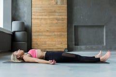 La jeune femme dans la classe de yoga, détendent la pose de cadavre de méditation Image libre de droits