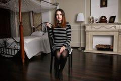 La jeune femme dans la robe rayée s'assied sur l'aChair parmi la chambre à coucher de luxe Photographie stock