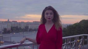La jeune femme dans la robe rouge marche près du parapet banque de vidéos