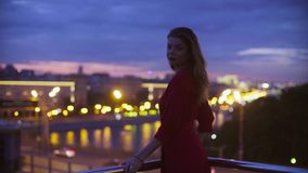 La jeune femme dans la robe rouge s'assied sur un parapet clips vidéos