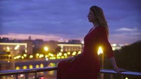 La jeune femme dans la robe rouge s'assied sur un parapet banque de vidéos