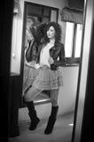 La jeune femme dans la veste en cuir noire et le tutu court gris bordent le regard dans un grand miroir Belle pose bouclée de fil Photographie stock libre de droits