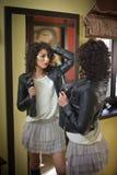 La jeune femme dans la veste en cuir noire et le tutu court gris bordent le regard dans un grand miroir Belle pose bouclée de fil Image stock