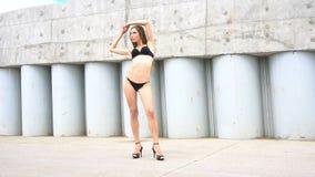 La jeune femme dans le bikini pose sur le fond du mur en béton banque de vidéos