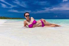 La jeune femme dans le bikini pourpre a couvert le sable menteur sur la plage Photographie stock libre de droits