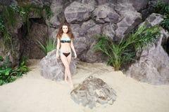 La jeune femme dans le bikini se tient sur le sable près aux roches photo stock