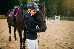 La jeune femme dans le casque étreint le cheval, équitation images stock